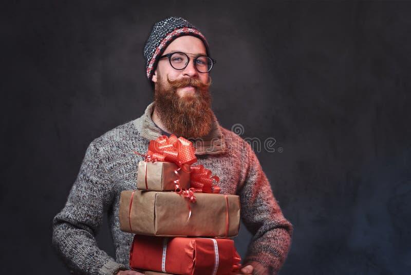 Het gebaarde mannetje houdt Kerstmisgiften stock fotografie