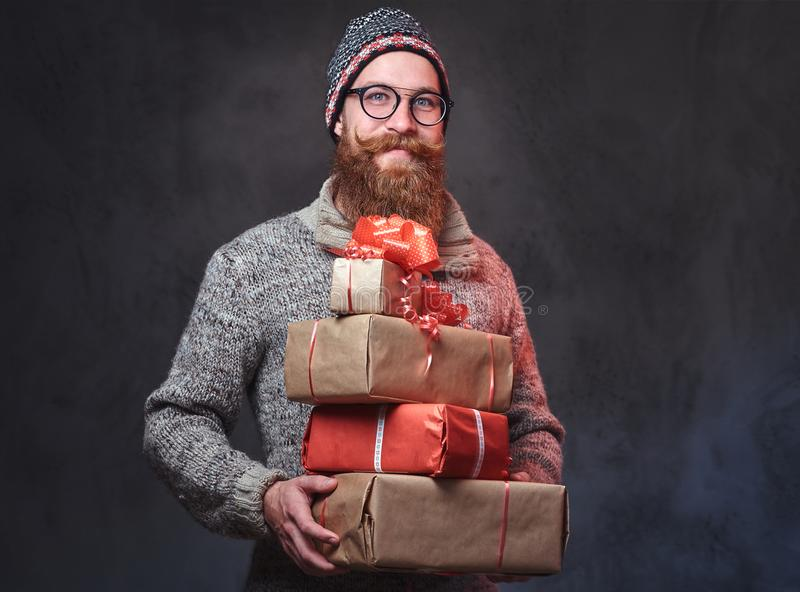 Het gebaarde mannetje houdt Kerstmisgiften stock foto's