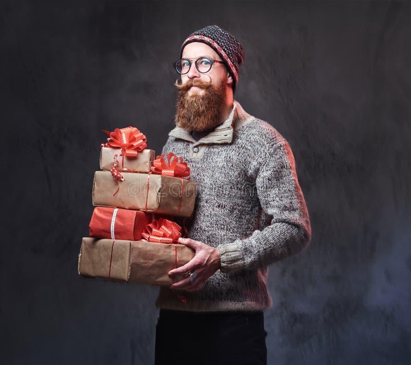 Het gebaarde mannetje houdt Kerstmisgiften stock afbeelding
