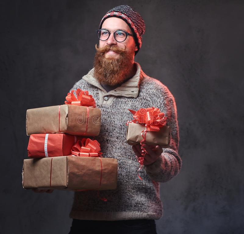 Het gebaarde mannetje houdt Kerstmisgiften royalty-vrije stock afbeelding