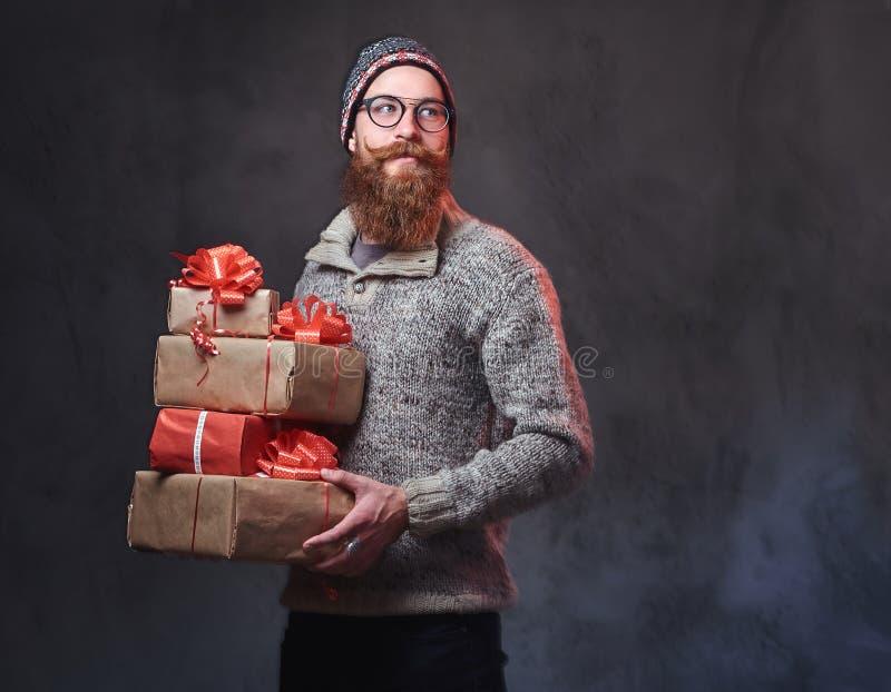 Het gebaarde mannetje houdt Kerstmisgiften royalty-vrije stock fotografie