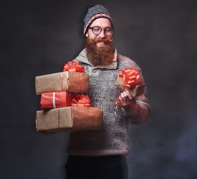 Het gebaarde mannetje houdt Kerstmisgiften royalty-vrije stock foto