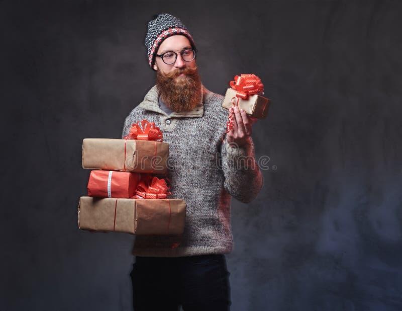 Het gebaarde mannetje houdt Kerstmisgiften stock afbeeldingen