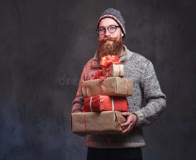 Het gebaarde mannetje houdt Kerstmisgiften stock foto