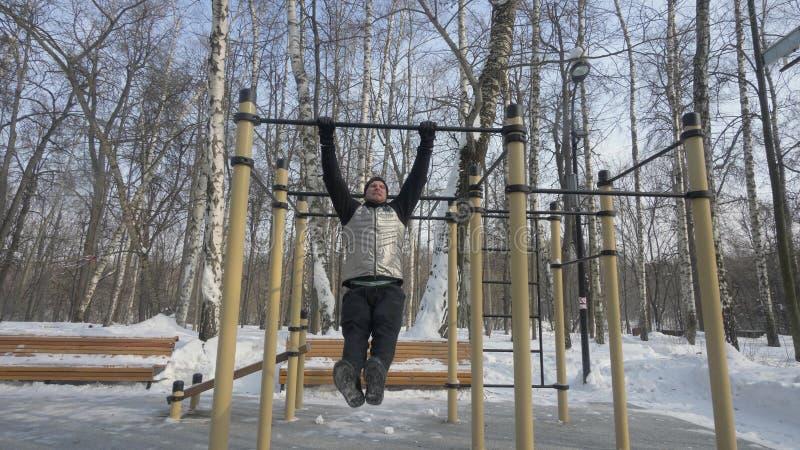 Het gebaarde mens doen trekt oefening tijdens openlucht opleiding op sportgrond uit stock fotografie