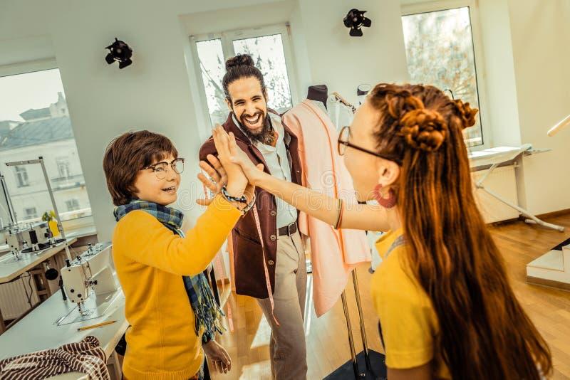 Het gebaarde vader gelukkig voelen lettend op zijn kinderen zijnd vrienden stock foto's