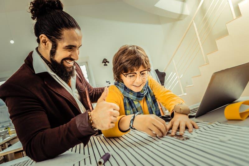 Het gebaarde vadergevoel stelde terwijl zijn zoon die hem helpen in atelier tevreden stock fotografie