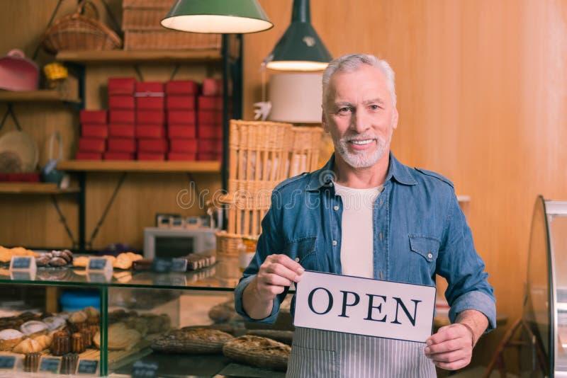 Het gebaarde zakenman vrolijk voelen openend zijn nieuwe Franse bakkerij stock afbeelding