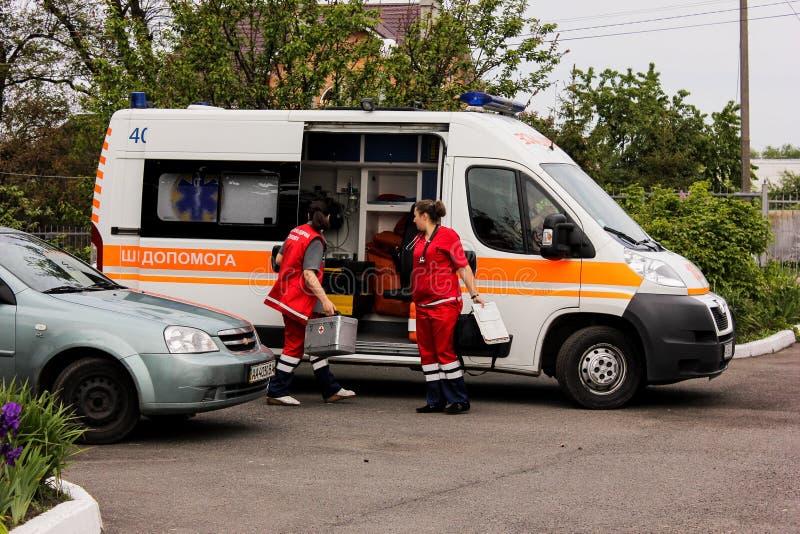 Het GEBIED van KIEV, de OEKRAÏNE - Mei 12, 2016: ziekenwagen en een verpleegster op de straat De ziekenwagen is dichtbij het ziek royalty-vrije stock foto