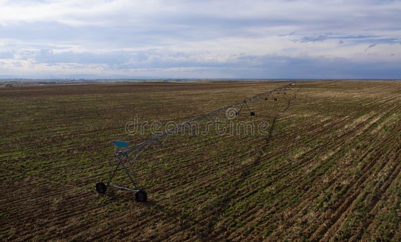 Het gebied van het landbouwbedrijf met irrigatiesysteem stock foto's