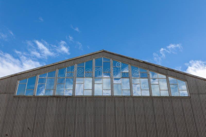 Het gebouw van het pakhuis met blauwe hemel die in vensters wordt weerspiegeld, die naar boven leiden royalty-vrije stock foto