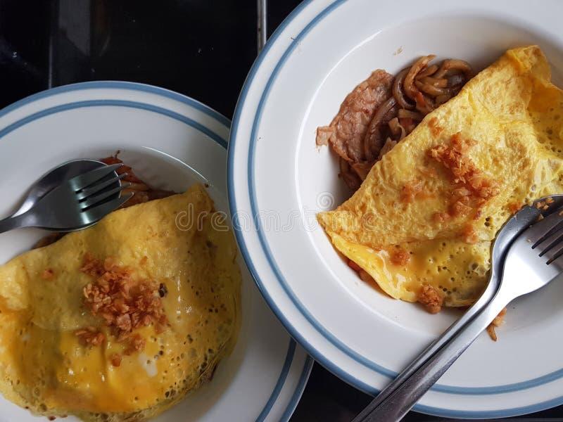Het gebraden ei met rijst en het varkensvlees dienen op witte plaat stock foto