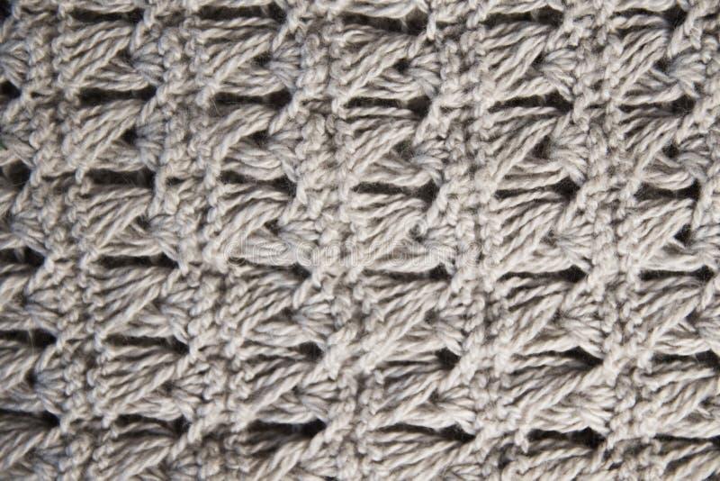 Het gebreide wollen textielcanvas van de sjaalkleding voor het beige bruine zandige natuurlijke materiaal van de ontwerpclose-up  royalty-vrije stock foto