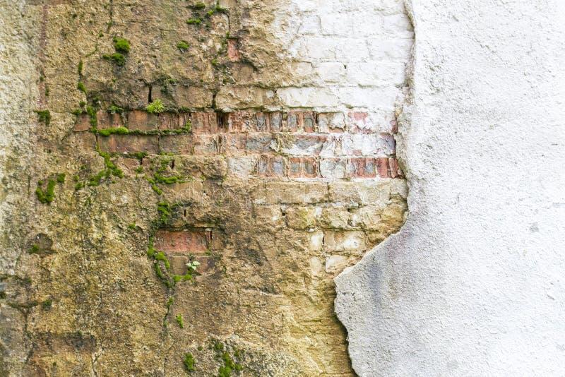 Het gebroken uitstekende fragment van de metselenmuur van oude rode kleibakstenen en beschadigde van het pleisterkader textuur al stock foto's