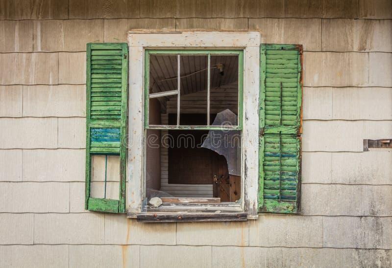 Het gebroken venster met groene blinden op oude die plattelander verliet schuur door helder dalingsgebladerte wordt omringd royalty-vrije stock foto