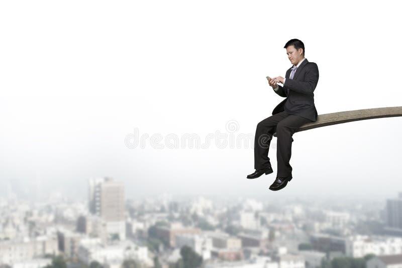 Het gebruiken van de mobiele zitting van de telefoonzakenman op springplank met citys royalty-vrije stock foto