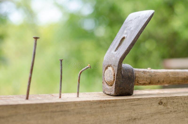 Het gebruiken van hamer en spijkers en gebogen spijker op hout en bokeh achtergrond stock afbeeldingen