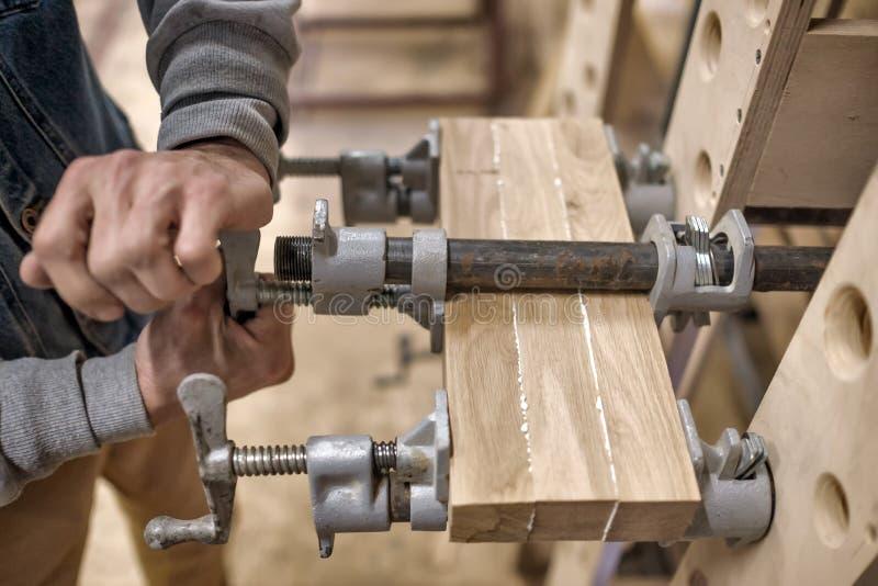 Het gebruiken van klemmen en lijm om houten hout voor meubilairdetail te verbinden royalty-vrije stock fotografie