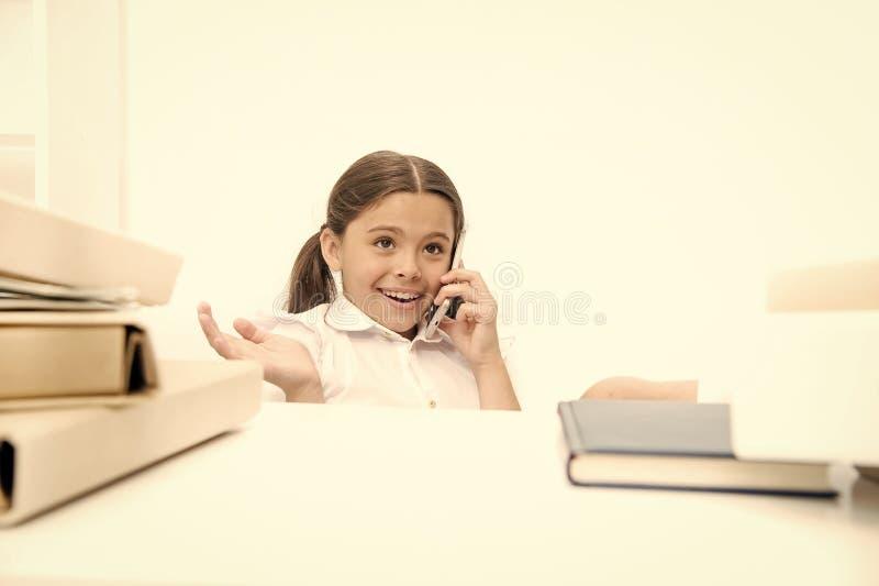 Het gebruiken van nieuwe communicatietechnologie in schoolonderwijs Klein meisje die op mobiele telefoon op les spreken Klein sch stock foto