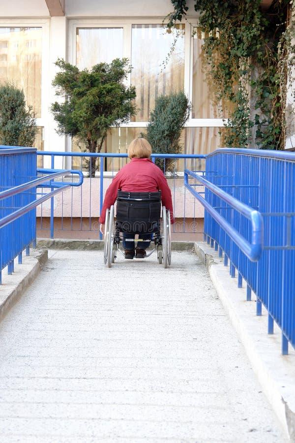 Het gebruiken van rolstoelhelling stock foto