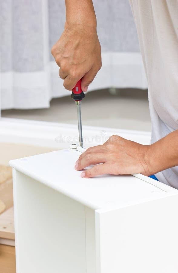Het gebruiken van Schroevedraaier Assembling Wooden Furniture stock afbeelding