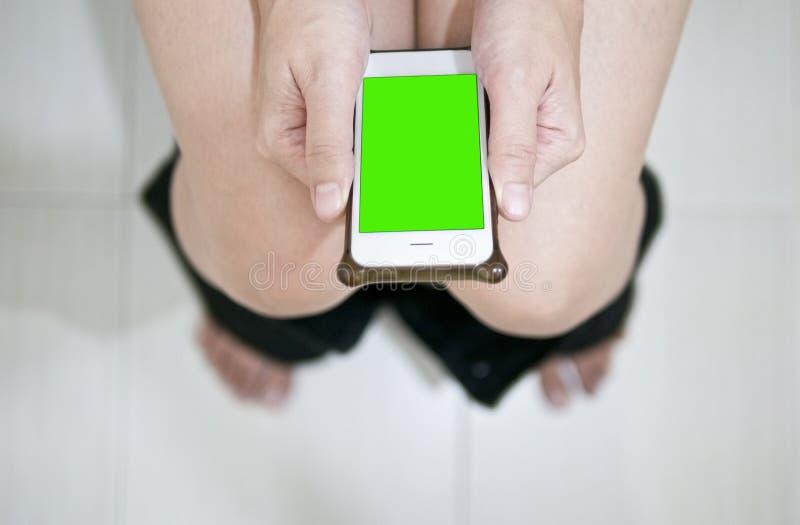 Het gebruiken van slimme telefoon terwijl het zuiveren royalty-vrije stock afbeeldingen