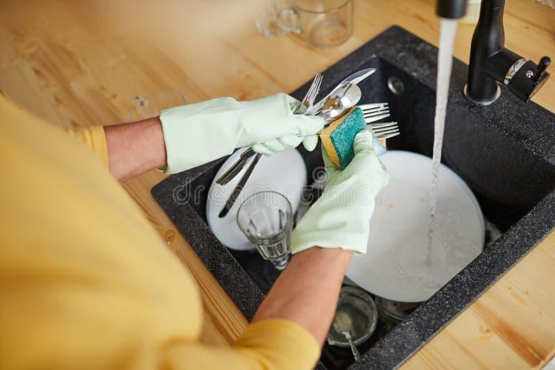 Het gebruiken van spons voor wasschotels stock foto