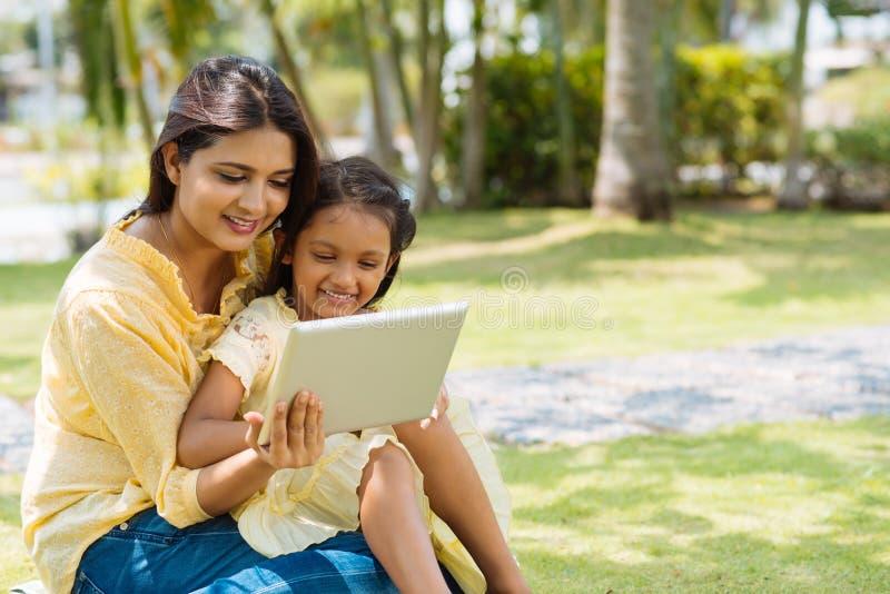 Het gebruiken van tablet in het park stock foto