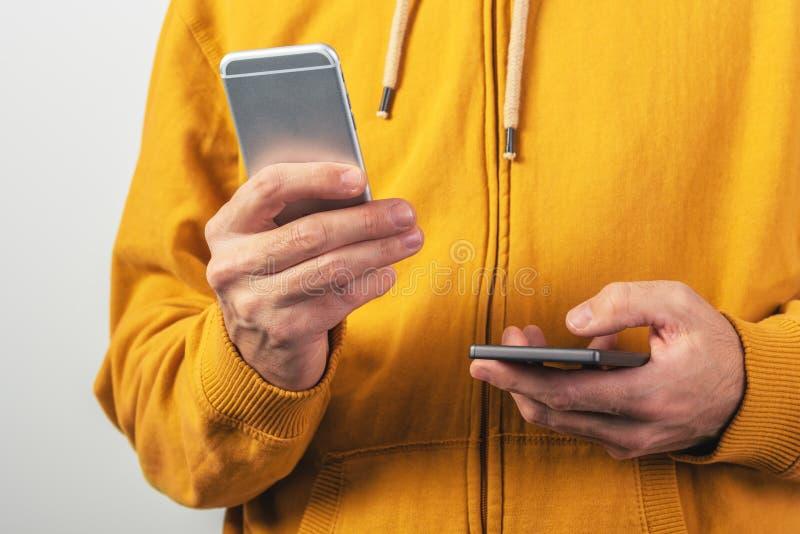 Het gebruiken van twee mobiele telefoons voor mededeling royalty-vrije stock afbeeldingen