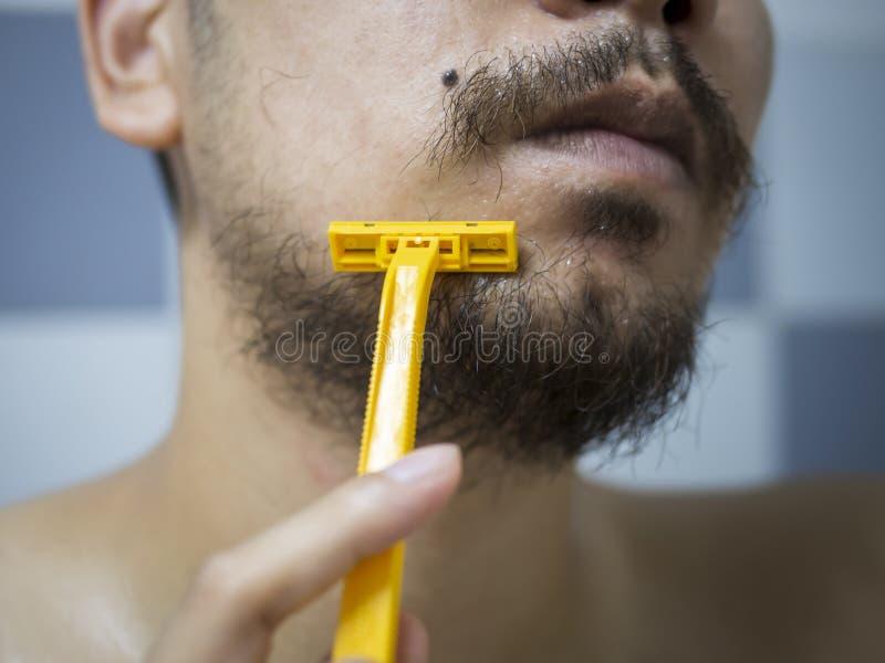 Het gebruiks geel scheerapparaat die van de close-upmens slordige baard en snor op zijn gezicht in badkamers scheren royalty-vrije stock foto