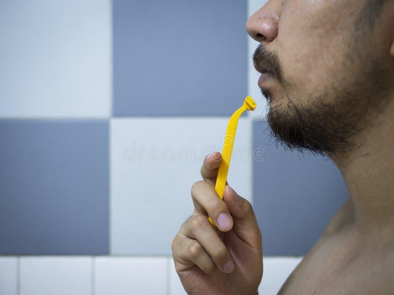 Het gebruiks geel scheerapparaat die van de close-upmens slordige baard en snor op zijn gezicht in badkamers scheren stock afbeelding