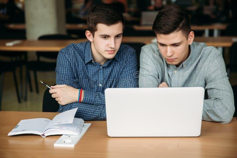 Het gebruikslaptop van de twee jongensstudent in bibliotheek Zij gebruiken laptop op een examen voor te bereiden studie royalty-vrije stock foto