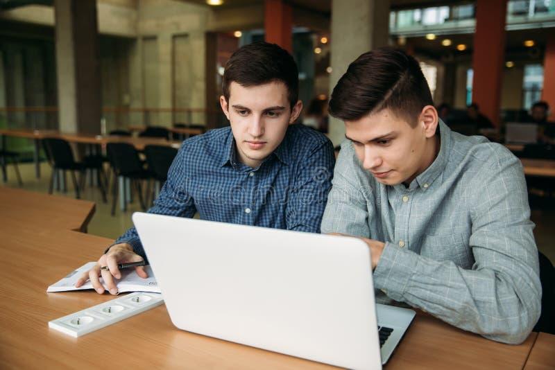 Het gebruikslaptop van de twee vriendenstudent in bibliotheek stock fotografie