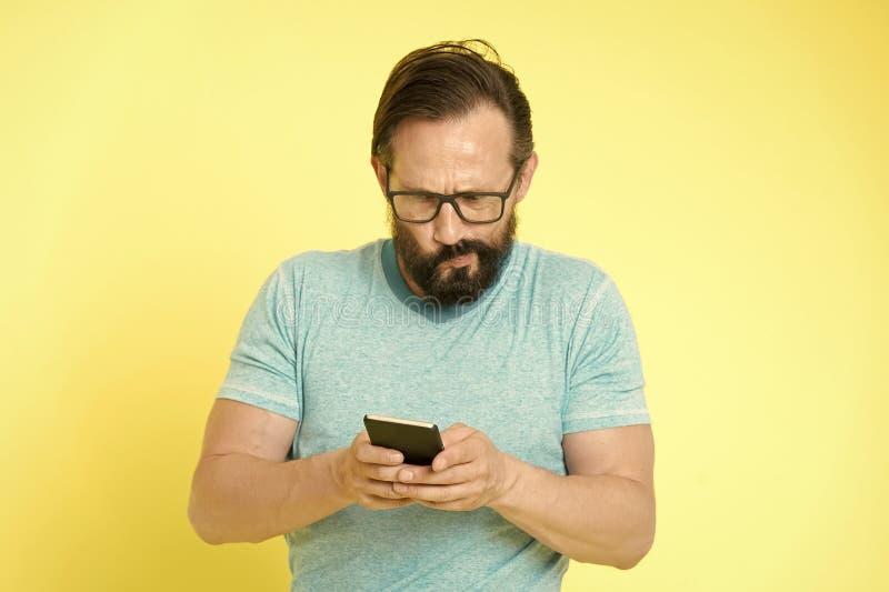 Het gebruikssmartphone van het kereloogglazen in verwarring gebrachte gezicht De mensengebruiker werkt toepassingssmartphone op e stock foto