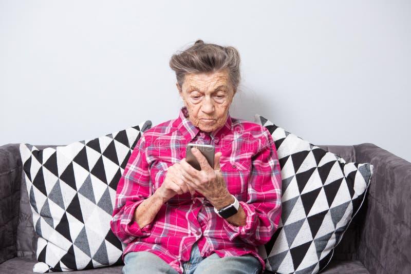 Het gebruikstechnologie van de thema oude persoon de oude grijs-haired Kaukasische vrouw met rimpels zit huis in woonkamer op ban stock afbeelding