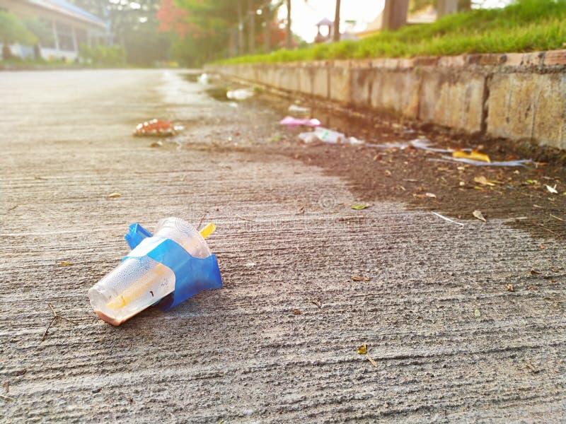 Het gebruikte plastic glas werd verlaten als huisvuil op de straat royalty-vrije stock afbeeldingen