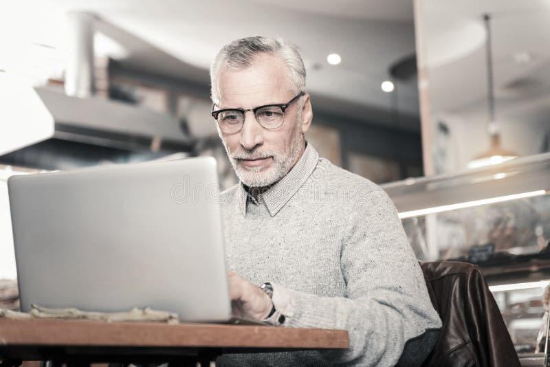 Het geconcentreerde freelancer recht bekijken zijn laptop royalty-vrije stock afbeeldingen