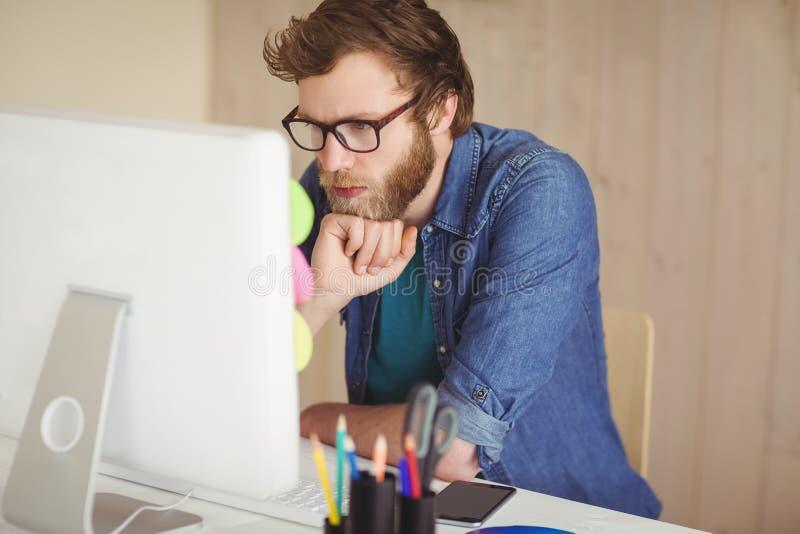 Het geconcentreerde hipster werken bij zijn bureau stock afbeelding