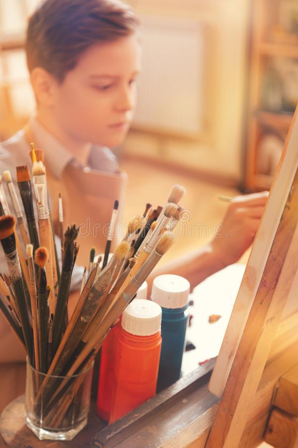 Het geconcentreerde jonge kunstenaar schilderen op kunstcanvas in studio royalty-vrije stock afbeelding