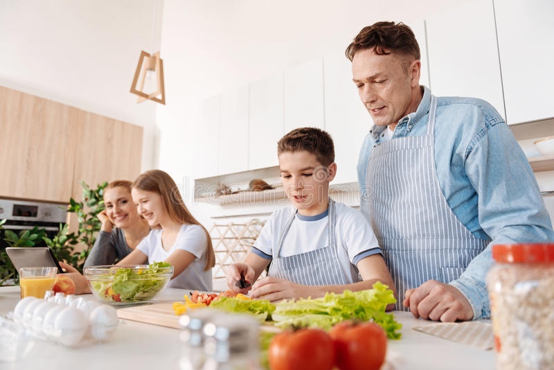 Het geconcentreerde jongen koken met zijn vader stock fotografie