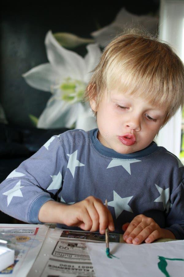 Het geconcentreerde jongen schilderen