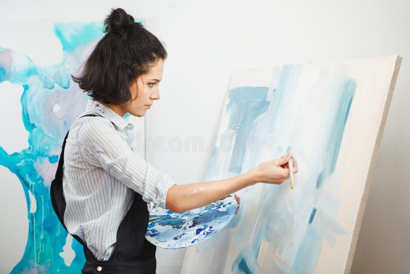 Het geconcentreerde meisje concentreerde zich op creatief kunst-makend proces in kunsttherapie stock afbeeldingen
