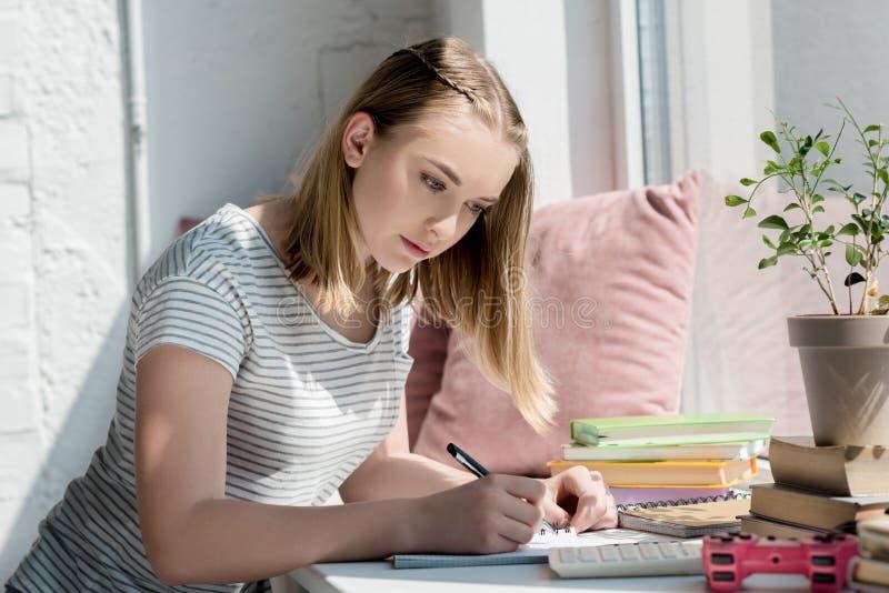 het geconcentreerde meisje die van de tienerstudent thuiswerk doen stock afbeelding