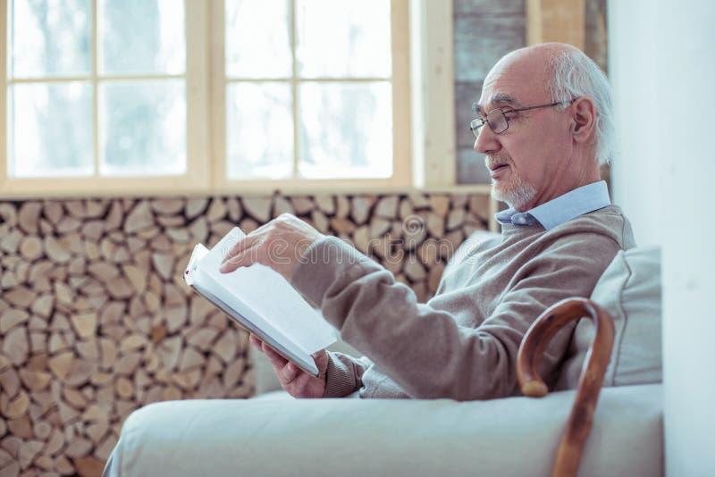 Het geconcentreerde rijpe boek van de mensenlezing thuis stock afbeeldingen