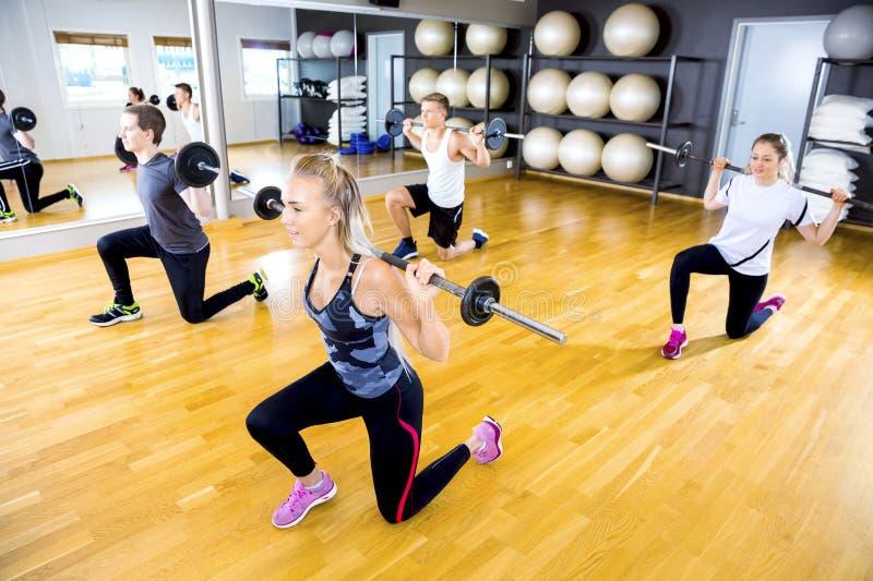 Het geconcentreerde team verdeelde hurkzit met gewichten bij geschiktheidsgymnastiek stock afbeelding