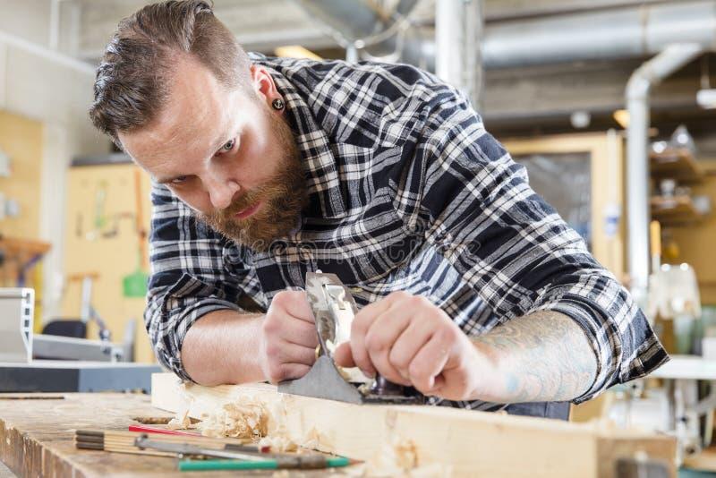 Het geconcentreerde timmermanswerk met vliegtuig op houten plank in workshop stock afbeeldingen
