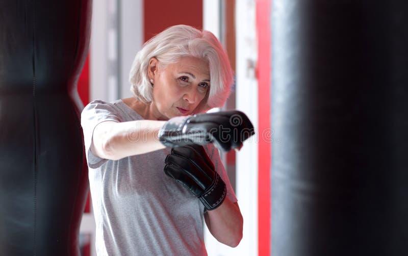 Het geconcentreerde vrij grijze haired vrouw in dozen doen in een gymnastiek stock afbeeldingen