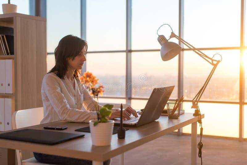 Het geconcentreerde vrouwelijke werknemer typen op het werk die computer met behulp van Zijaanzichtportret van een tekstschrijver royalty-vrije stock fotografie