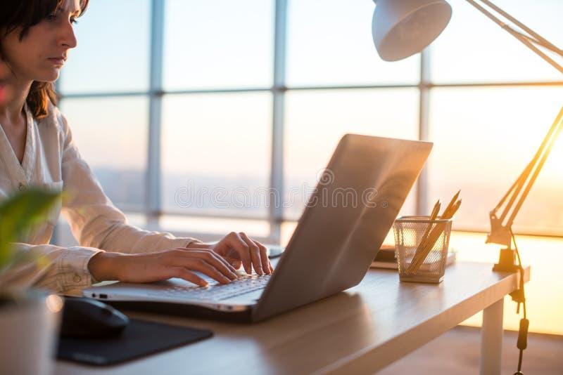 Het geconcentreerde vrouwelijke werknemer typen op het werk die computer met behulp van Zijaanzichtportret van een tekstschrijver stock foto