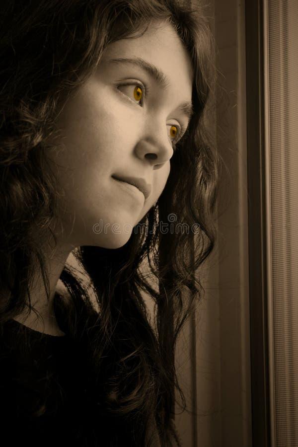 Het gedeprimeerde kijken uit venster gouden ogen stock foto